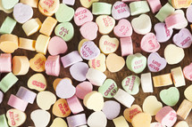 Candy hearts scattered on a wood table.
