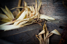 Harvested corn tassels and flint corn cover wooden planks.