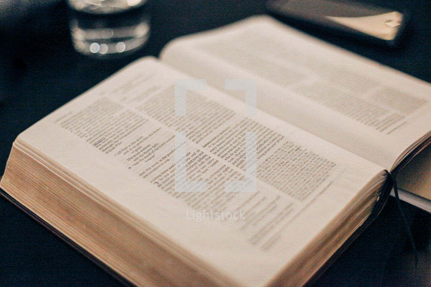 open Bible on a table with a glass of water and journal