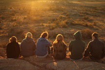 friends sitting at the edge of a cliff in a desert landscape at sunset