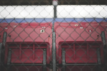 Stadium seats behind a chain link fence.