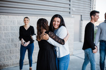 two women hug in front of a church