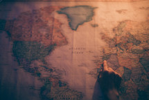 hand pointing to a world map