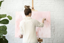 A woman painting on a canvas