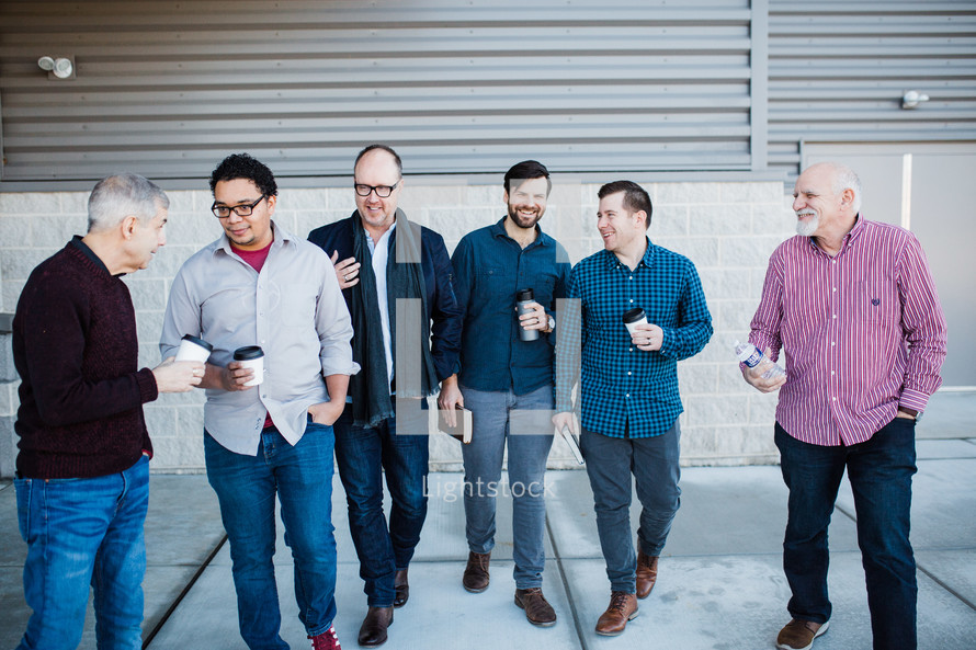 men standing in front of a church talking holding coffee cups