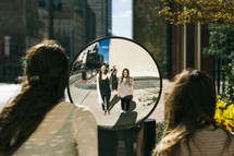 two girl looking into a mirror on a sidewalk