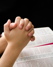 A child's praying hands over a Bible