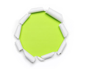Green showing through a circle of torn white paper.