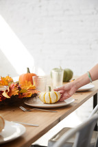 woman setting a table for a fall dinner party