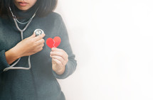 a woman holding a broken heart listening to her own heart with a stethoscope