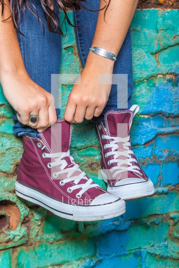teen girl adjusting her converse sneakers