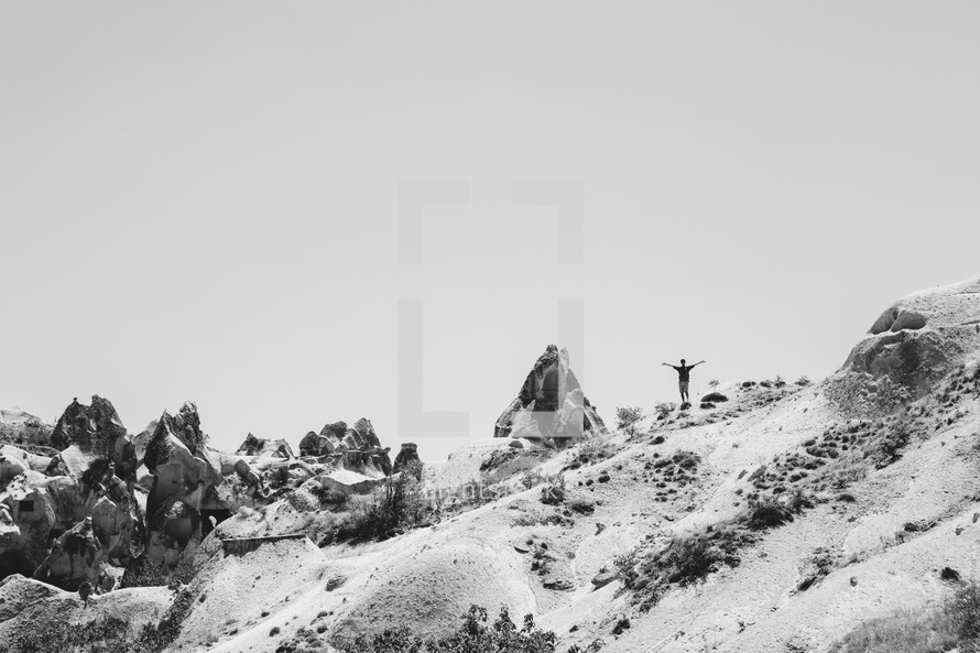 a man standing with open arms on a mountaintop