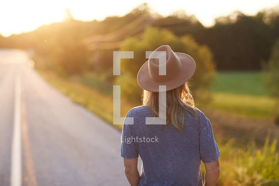 a woman in a hat walking down a rural road
