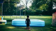 a little boy standing in a sprinkler