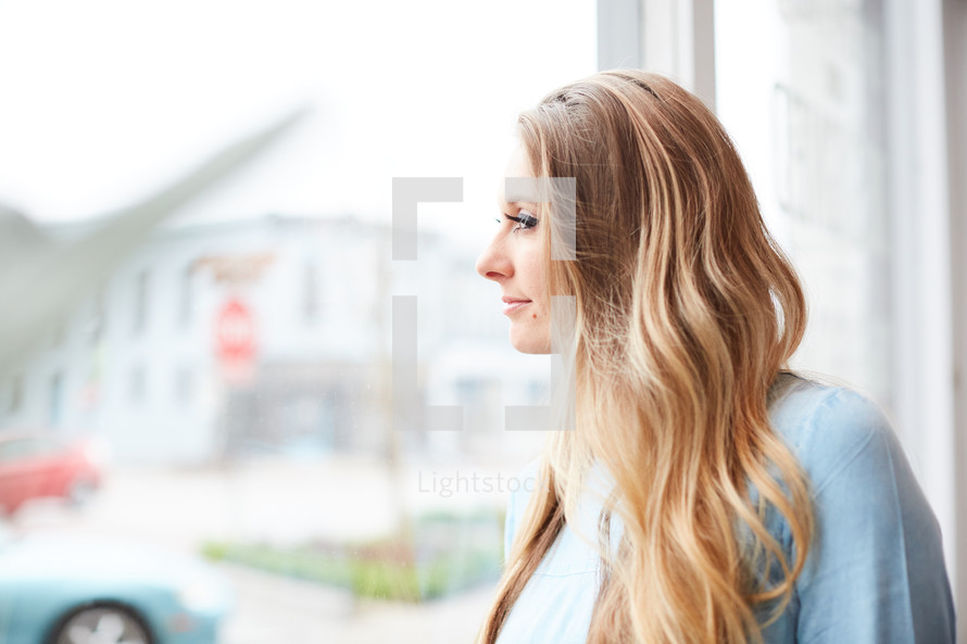 a young woman standing in front of a window daydreaming