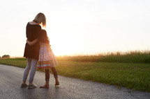 a mother and daughter hugging outdoors