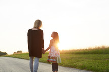 a mother and daughter talking outdoors at sunset