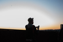 Silhouette of a man using an iphone outside at sunrise.
