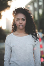 a young african-american woman standing under intense sunlight outdoors