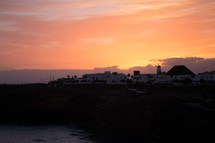 Sunset over a village next to the ocean.