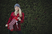 a woman holding a Christmas stocking outdoors