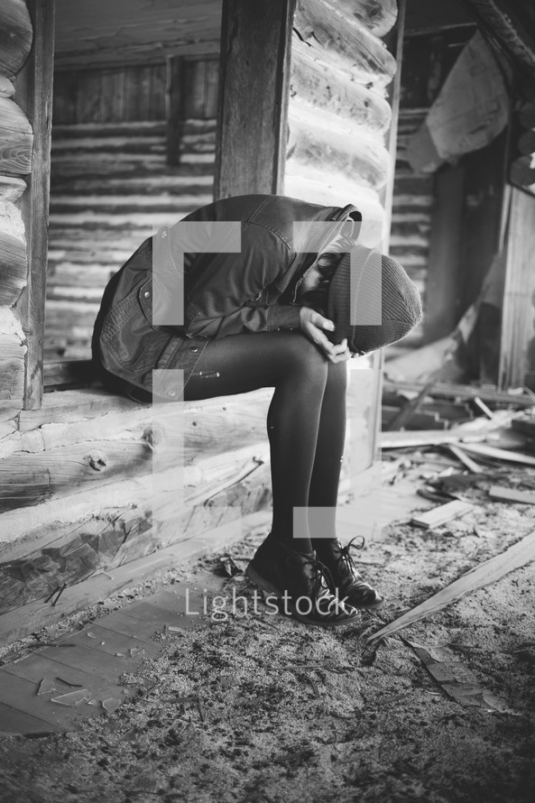 A woman sitting in a log house with her head in her hands.