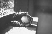 baseball in a glove in a dugout
