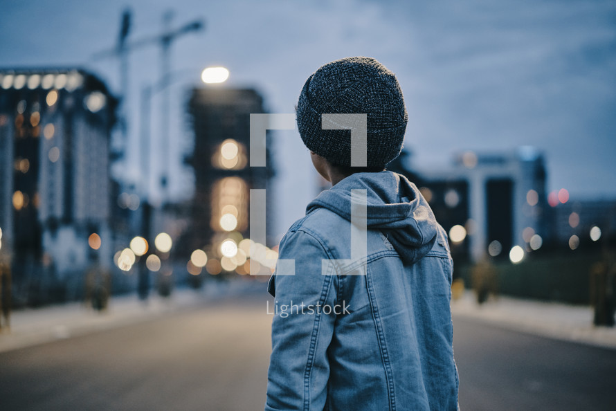 a young boy standing in the middle of a road looking back at a city