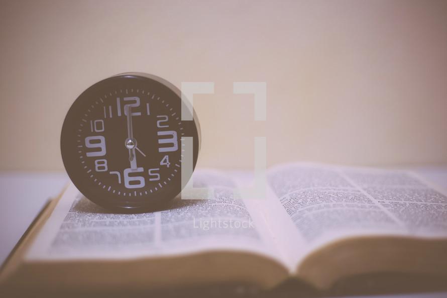 wall clock on an open Bible