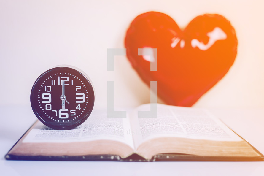wall clock on an open Bible with a heart