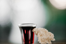 communion wine in a cup and bread against a bokeh background