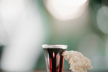 communion wine in a cup and bread on bokeh background