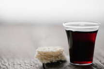 communion wine in a cup and bread on white background