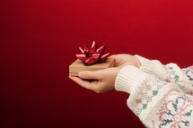 cupped hands holding a Christmas gift box