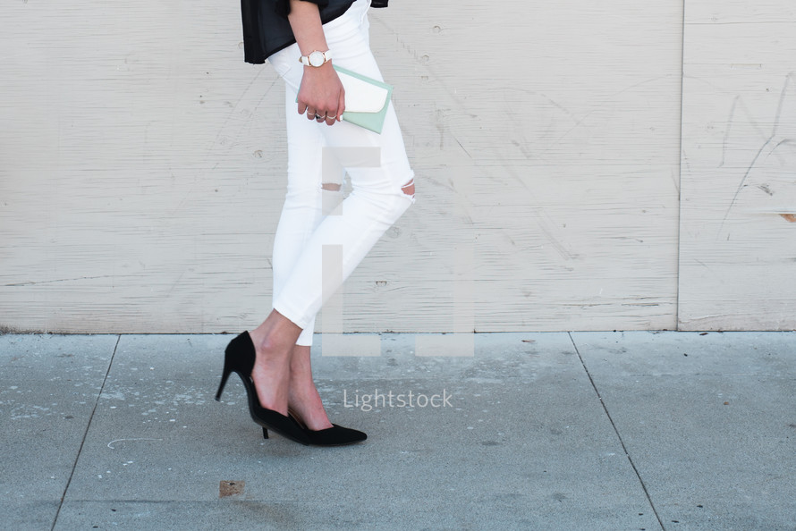 a woman walking with a clutch purse