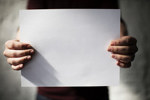 man holding a piece a blank white paper