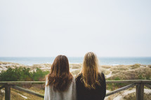 two women looking over a railing at a beach