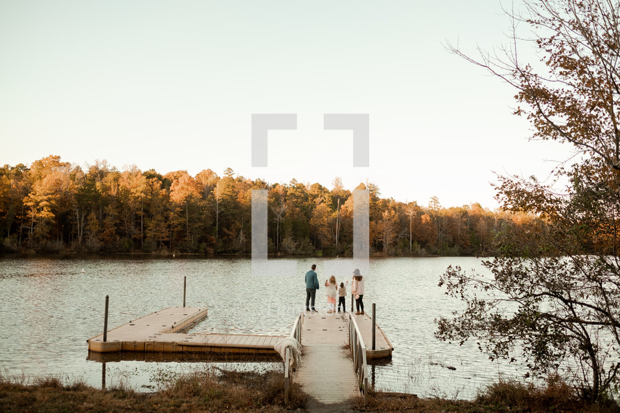a family standing on a dock in fall