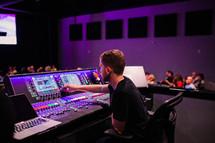 sound production team behind a soundboard