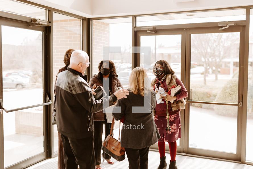fellowship in a church narthex with face masks