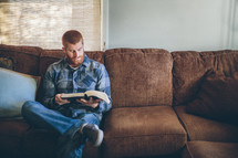 man reading a Bible while sitting on a couch