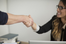 a businesswoman shaking hands and greeting someone in the office.