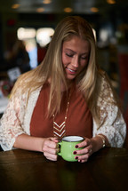 a woman drinking coffee in a sweater