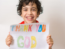 "Smiling boy holding a sign reading  ""thank you God""  written in crayon."