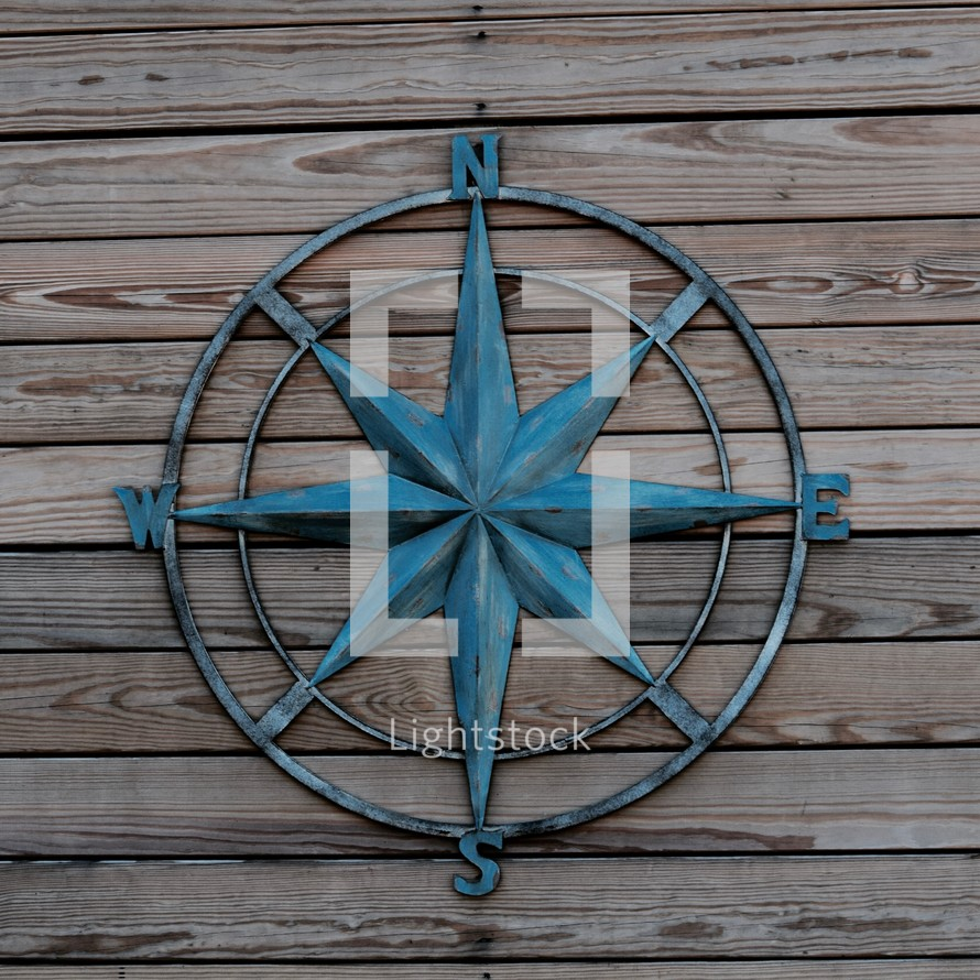 metal sculpture compass rose against wood boards