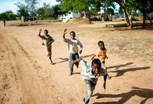 children running after a moving vehicle
