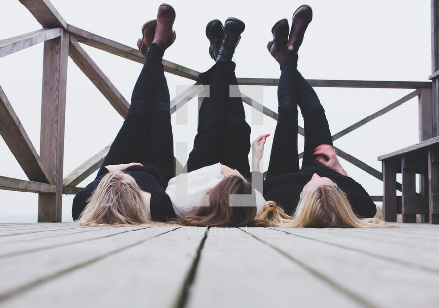 three women lying on a wood deck