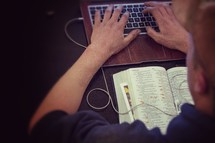 man typing on a keyboard and an open Bible