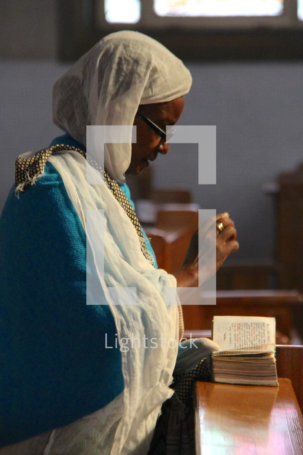 An elderly Ethiopian Orthodox woman in prayer