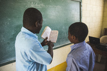 Teacher in front of chalkboard in a classroom reading with a student.